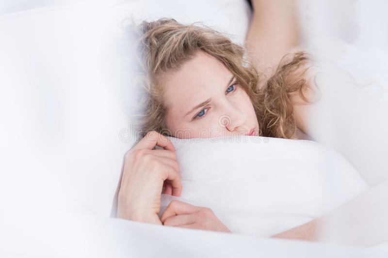 Frustrated female lying in bed stock photography