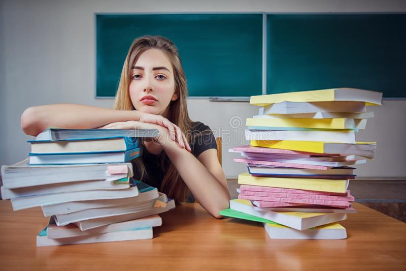 Frustrated female student sitting at the desk with a huge pile of study books in classroom. stock photos