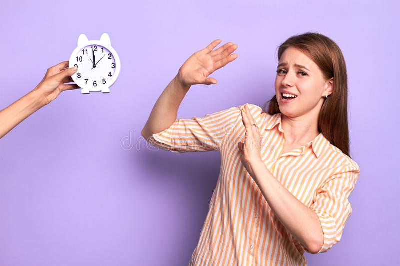 Frustrated female student trying to hide from alarm clock, deadline is overdue stock photography