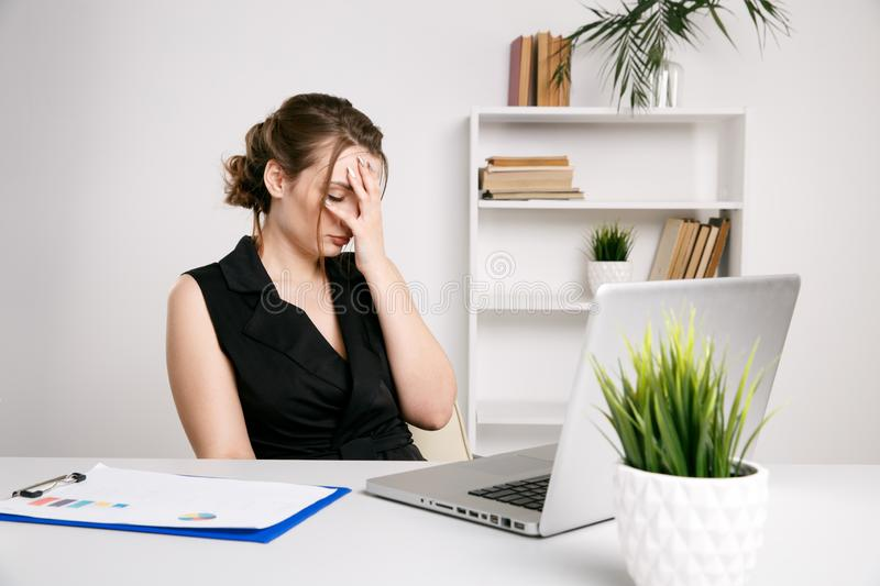 Frustrated female worker in office ather desk. Sick and tired woman. stock photography