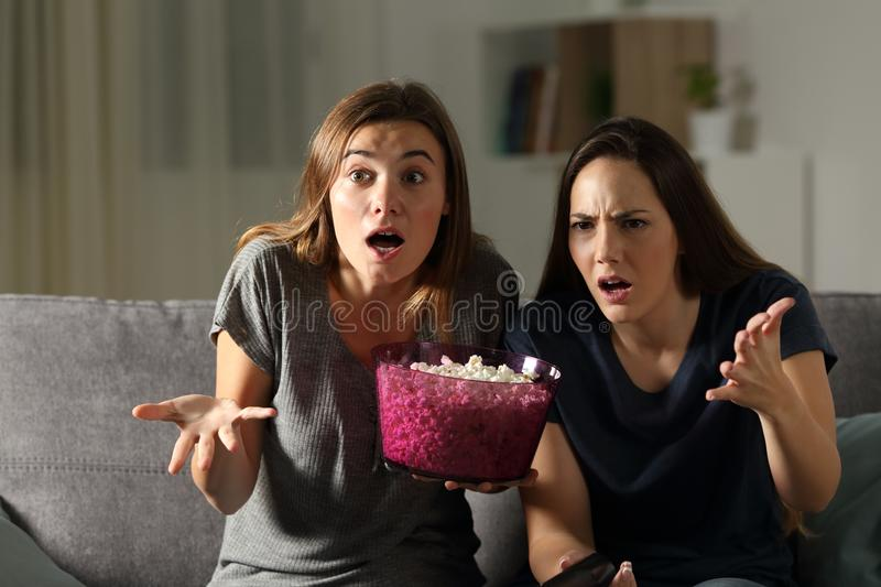 Frustrated friends watching tv in the night. Sitting on a couch in the living room at home stock photography