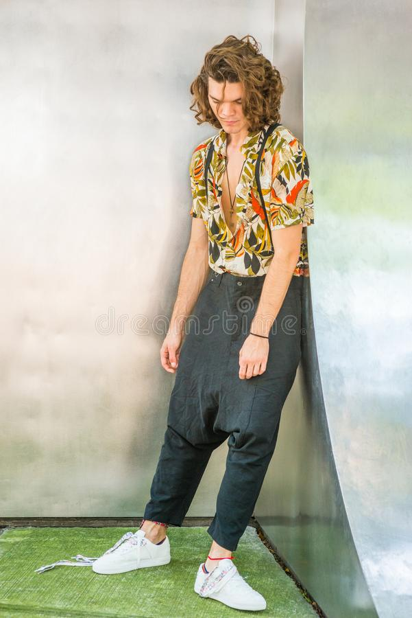 Frustrated Hispanic American Artist with brown curly hair in New. York, wearing colorful patterned short sleeve shirt, baggy loose pants with suspenders, white stock photography