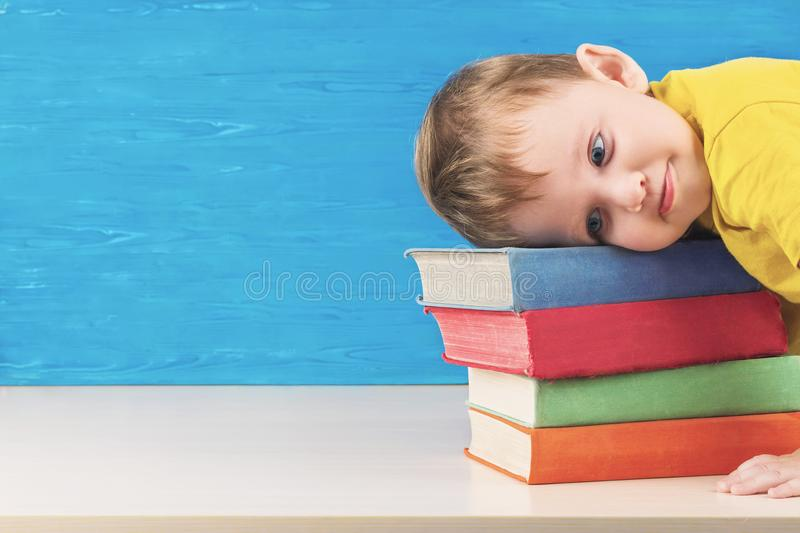 The frustrated little boy put his head on a bunch of textbooks. Back to school. Doesn`t want to do his homework. stock photos