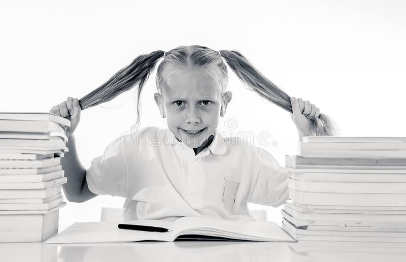 Frustrated little schoolgirl feeling a failure unable to concentrate in reading and writing difficulties learning problem stock photo