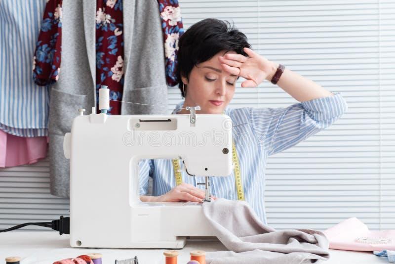Frustrated müde Näherin, die ihren Kopf, Gefühl absolut erschöpft wegen der Überlastung, arbeitend am Schneidergeschäft mit zu wä stockfotos