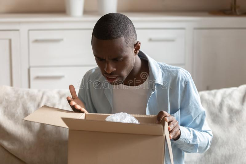 Frustrated male client feel disappointed with bad quality product. Frustrated mad african American man unpack cardboard box post shipping parcel with wrong order royalty free stock photos