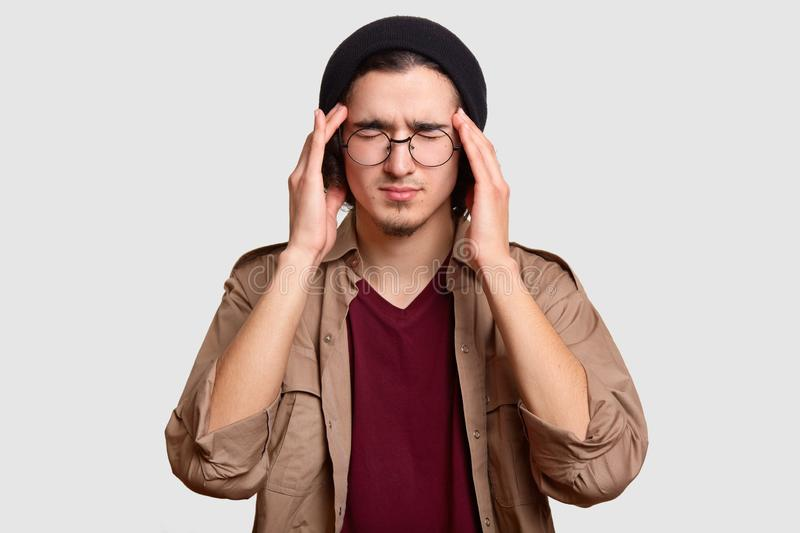 Frustrated male guy keeps hands on temples, suffers from headache, closes eyes from pain, has migraine after noisy party, wears bl royalty free stock image