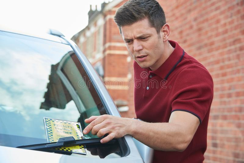 Frustrated Male Motorist Looking At Parking Ticket royalty free stock photos