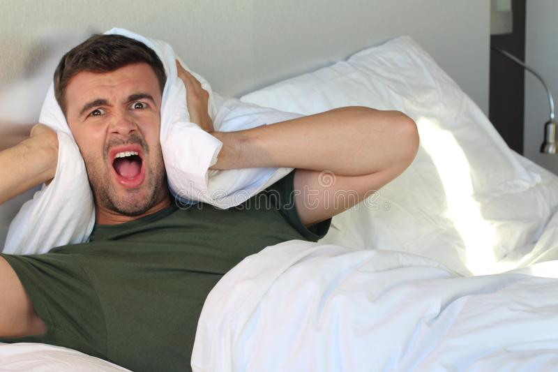 Frustrated man covering his ears with pillow royalty free stock photos