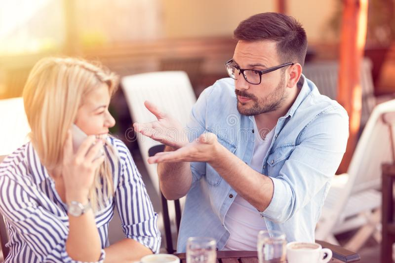 frustrated man criticizes his girlfriend who constantly talks over the phone stock images