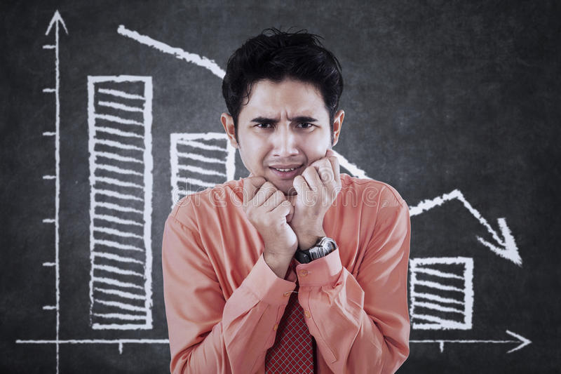 Frustrated man and falling graph. Photo of a frustrated young businessman looks fear and standing in front of declining graph royalty free stock image