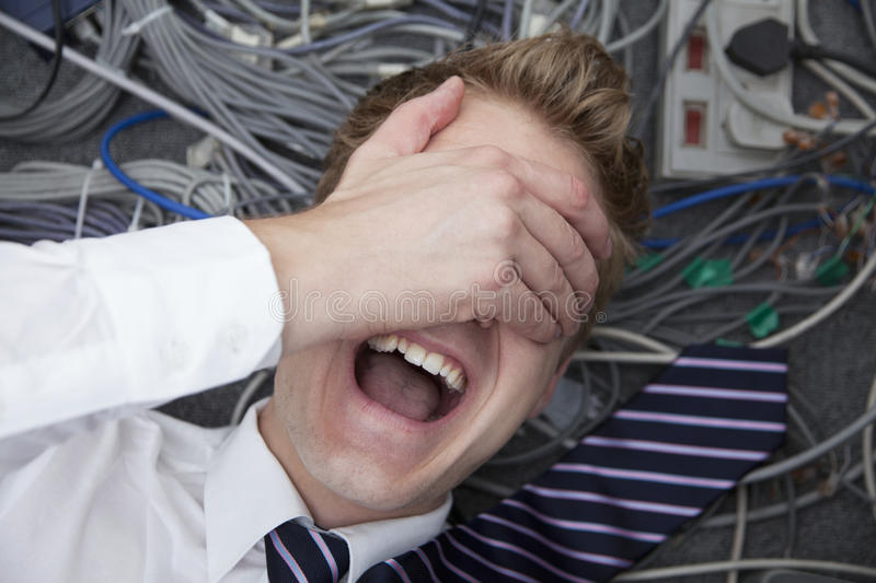 Frustrated man lying down covering his eyes surrounded by computer cables stock photography