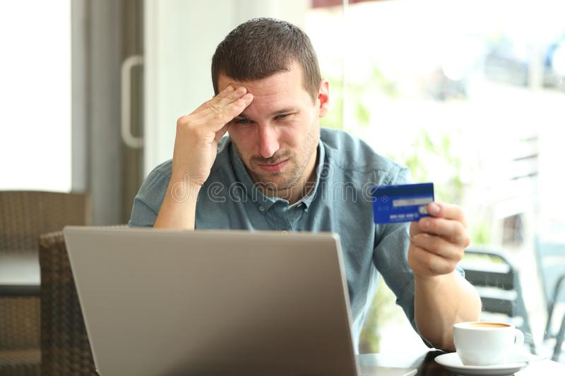Frustrated man paying with credit card and laptop in a bar. Frustrated man paying with credit card and laptop sitting in a coffee shop royalty free stock photos