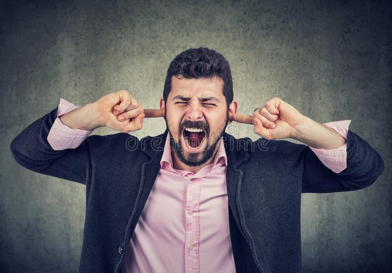 Frustrated man plugging his ears with fingers royalty free stock photo