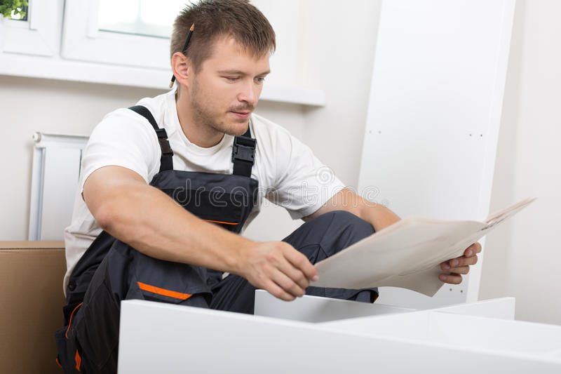 Frustrated man reading instruction. And putting together self assembly furniture. DIY, new home and moving concept stock photo