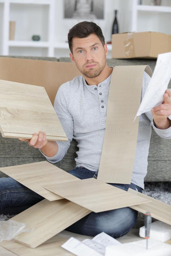 Frustrated man reading instruction and putting together self assembly furniture stock photos