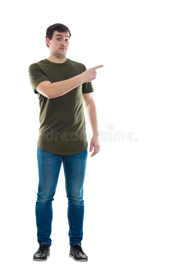 Frustrated man showing finger. Full length portrait frustrated casual young man pointing index finger showing something isolated over white background with copy stock photos