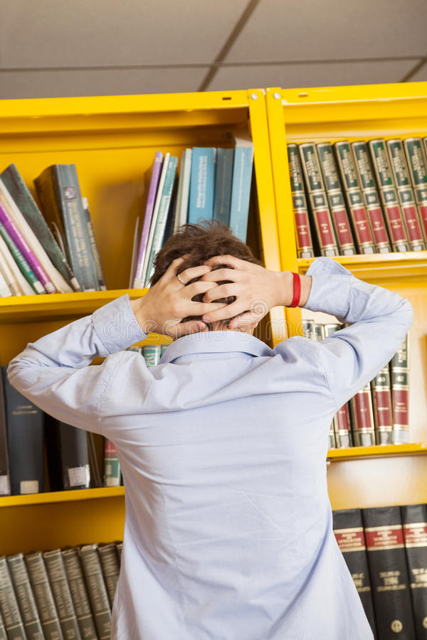 Frustrated Man Standing Against Bookshelf In stock photo