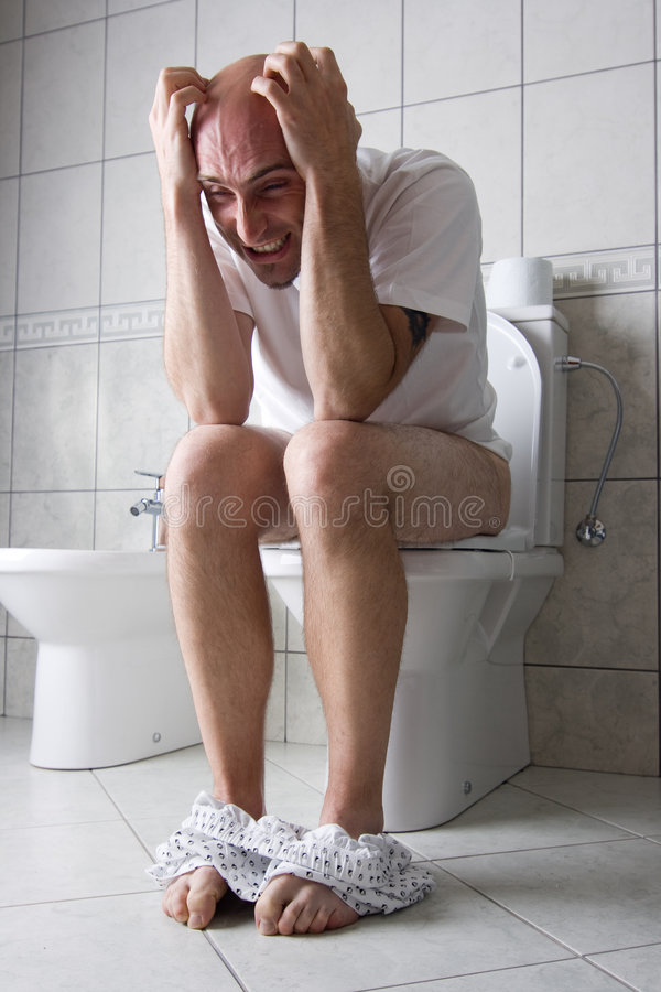 Frustrated man on toilet seat. A caucasian adult man with frustrated expression while on toilet seat with his boxers around his ankles. Wearing white shirt and royalty free stock photo