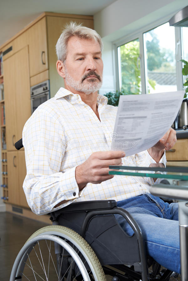 Frustrated Man In Wheelchair At Home Reading Letter. Man In Wheelchair At Home Reading Letter stock photos