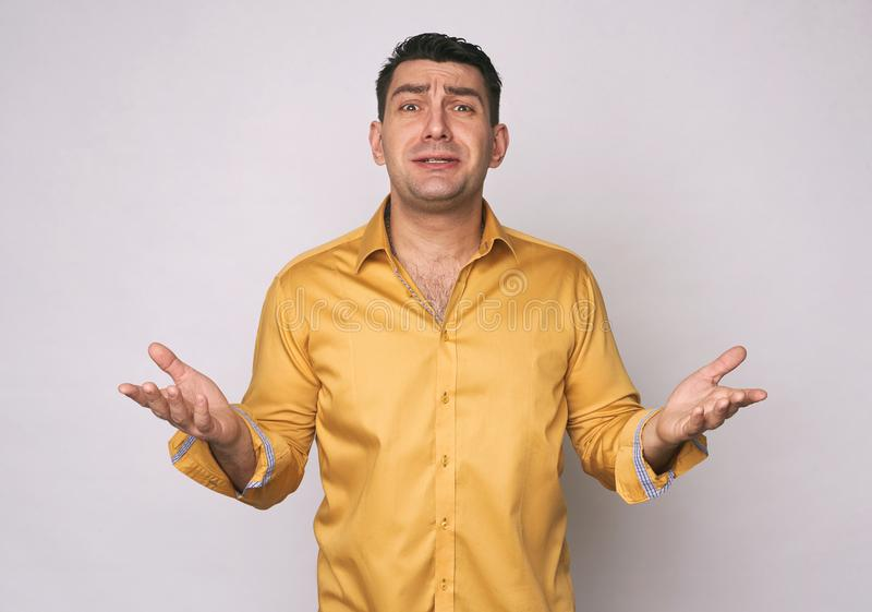 Frustrated man in yellow shirt isolated. On grey background royalty free stock photos