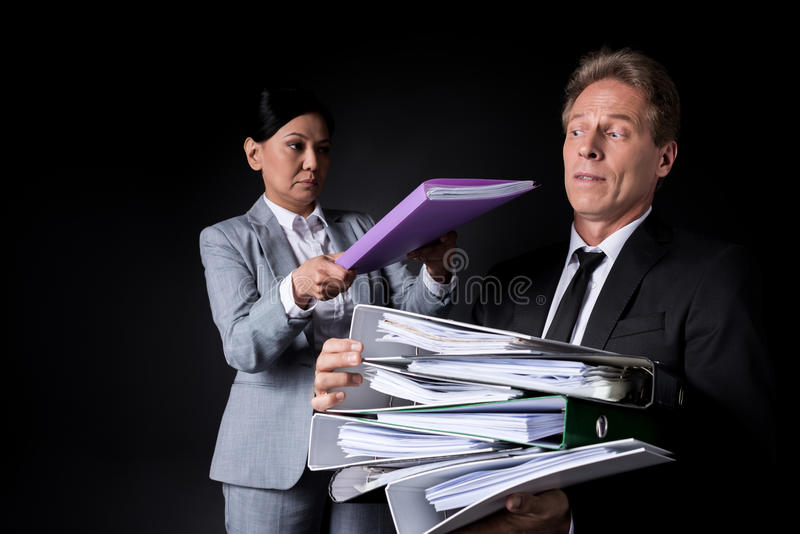 Frustrated mature businessman holding pile of folders while female colleague putting folder on the top. Isolated on black stock photos