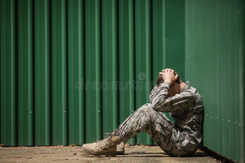Frustrated military soldier sitting with hands on head. In boot camp royalty free stock images