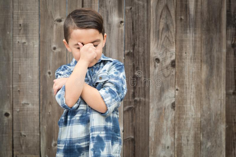 Frustrated Mixed Race Boy With Hand on Face. Young Frustrated Mixed Race Boy With Hand on Face Against Wooden Fence stock photos
