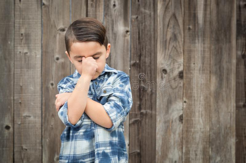 Frustrated Mixed Race Boy With Hand on Face. Young Frustrated Mixed Race Boy With Hand on Face Against Wooden Fence stock photo