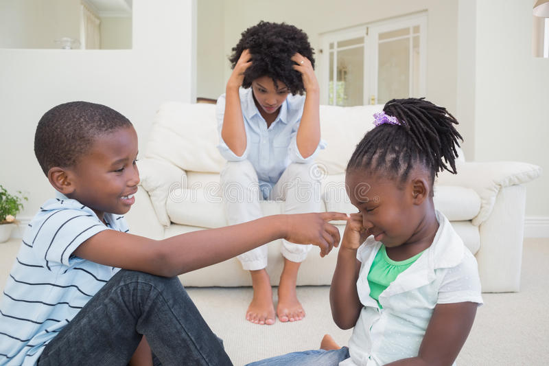 Frustrated mother watching children fight stock photo