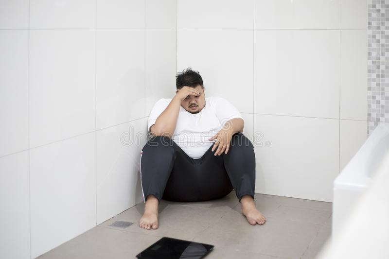 Obese Man With Scale And App Of Weight Loss Stock Photo