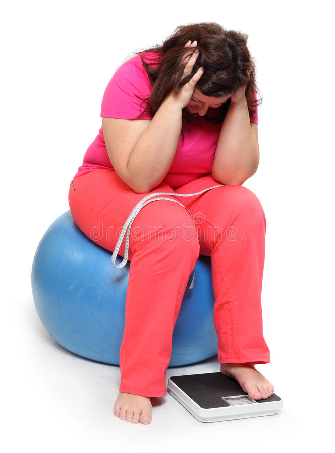 Frustrated obese woman. Overweight woman with weighing machine stock photography