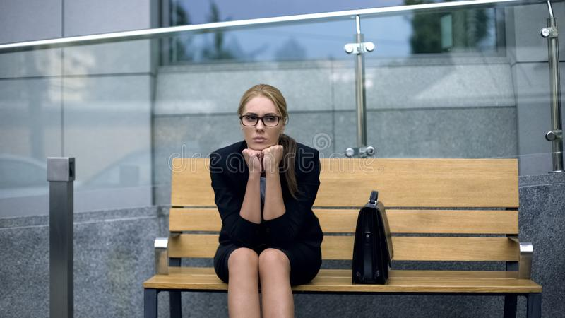 Frustrated office employee sitting on bench, tired after stressful meeting. Stock photo stock photography