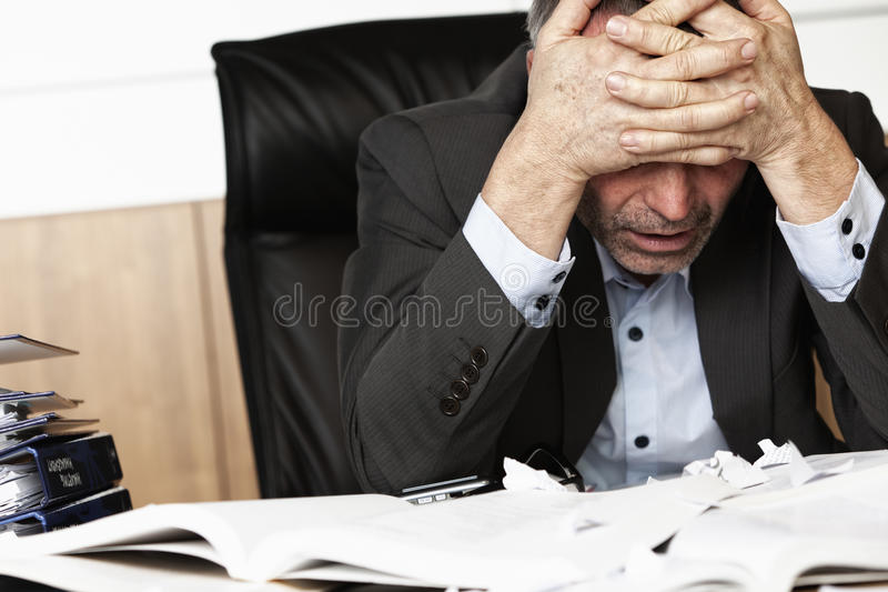 Frustrated office manager overloaded with work. Worried businessman sitting at office desk full with books and papers being overloaded with work stock photos