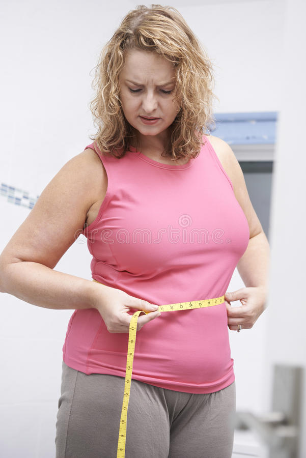 Frustrated Overweight Woman Measuring Waist In Bathroom royalty free stock photo