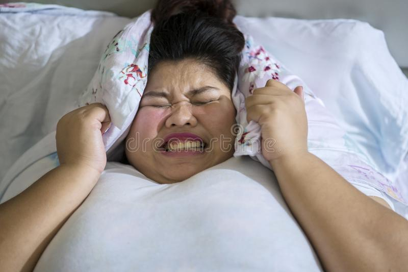 Frustrated overweight woman unable to sleep. Sleeping disorder concept; Frustrated overweight woman unable to sleep closing her face with a pillow stock photos