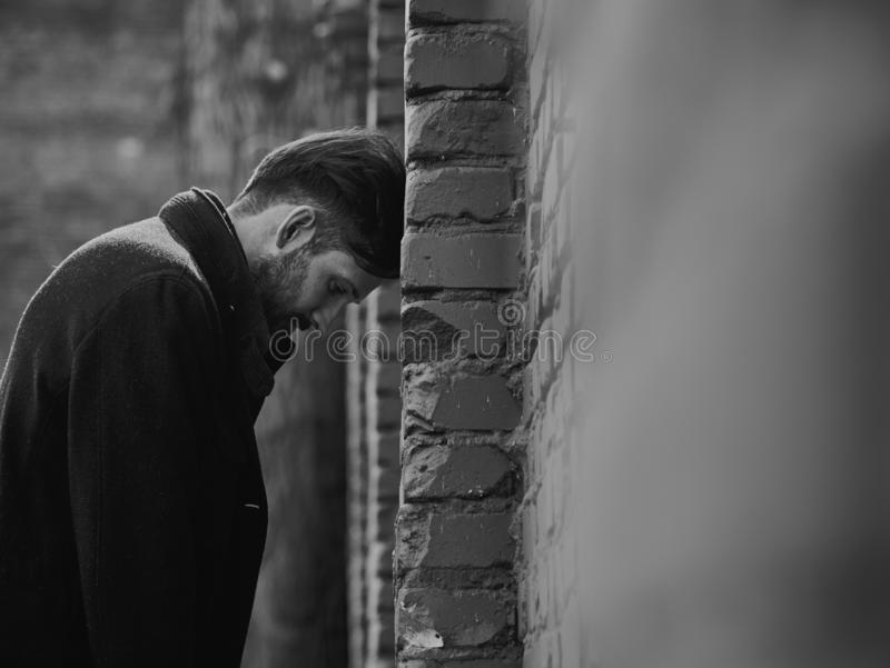 Frustrated presion? al hombre joven cerca de la pared de ladrillo que parec?a enojada Retrato dramático entonado triste del prime foto de archivo libre de regalías