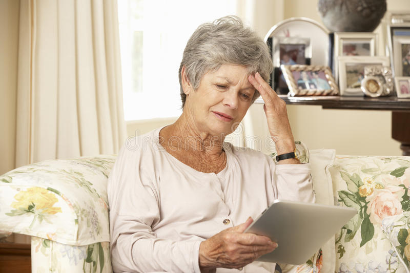 Frustrated Retired Senior Woman Sitting On Sofa At Home Using Digital Tablet royalty free stock images
