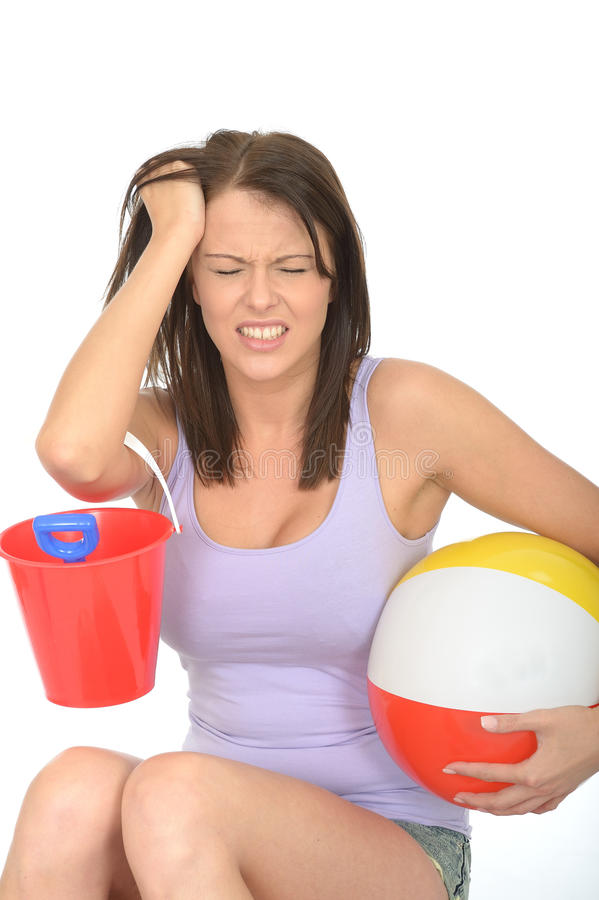 Frustrated Stressed Unhappy Young Woman on Holiday Holding a Bucket and Spade with Beach Ball royalty free stock photo