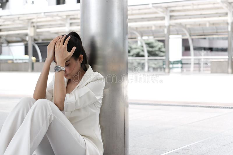 Frustrated stressed young Asian business woman with hands on face sitting at outdoors stock photos