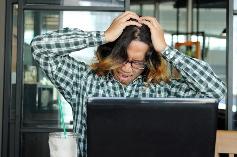Frustrated stressed young Asian man in casual clothes feeling stress in office. stock image
