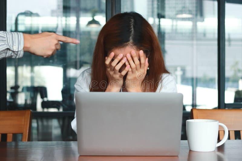 Frustrated subrayó negocio asiático joven con la cubierta está siendo jefe acentuado del ` s de la mano en lugar de trabajo fotografía de archivo libre de regalías