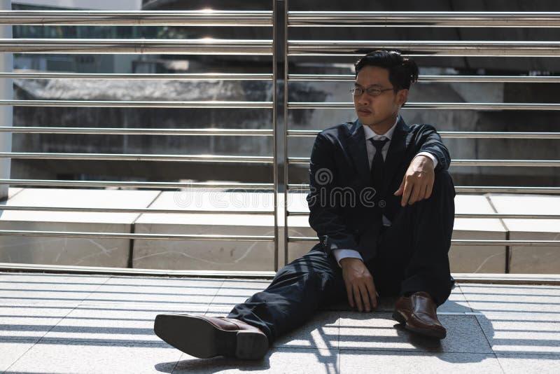 Frustrated subray? al hombre de negocios asi?tico joven que sufr?a de la depresi?n severa Desempleo y concepto del despido fotos de archivo