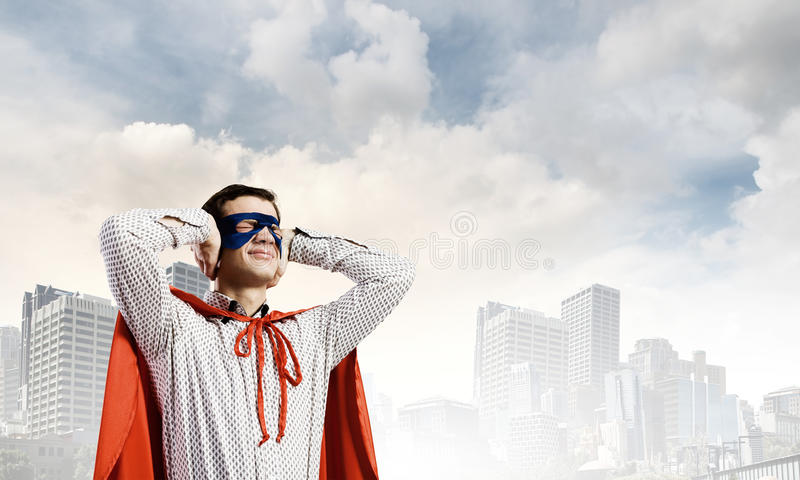 Frustrated superman. Young man in hero costume closing ears with palms stock photography