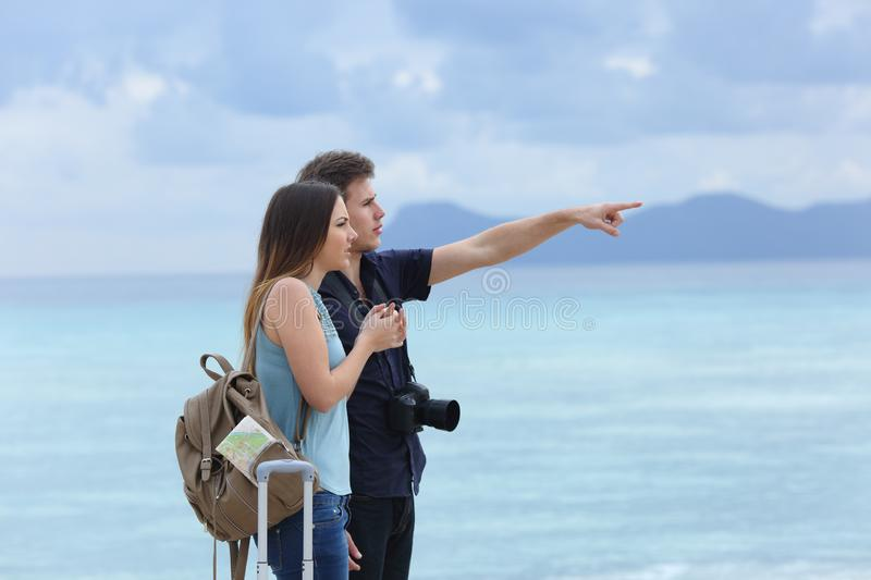 Frustrated tourists pointing horizon a bad day. Side view portrait of two frustrated tourists pointing horizon a bad cloudy day on vacation stock photography