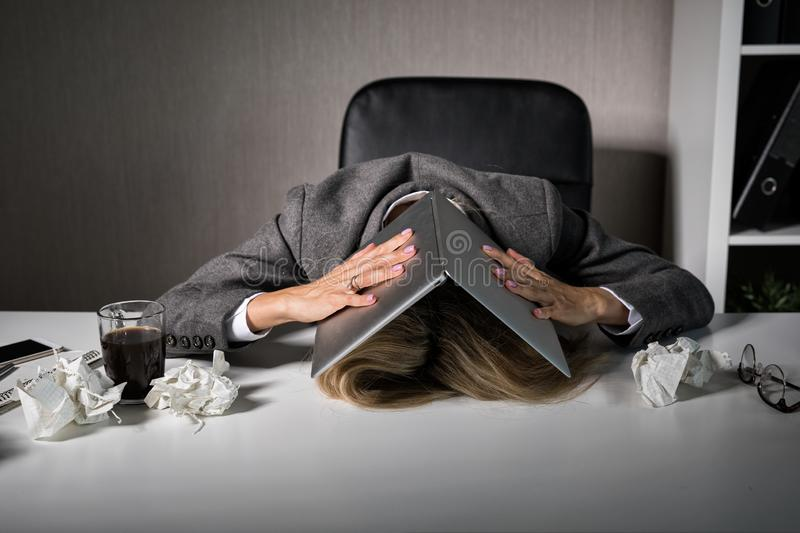 Frustrated woman hiding under laptop in office stock photo