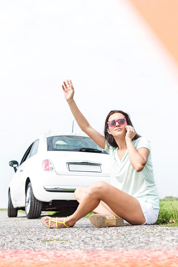 Frustrated woman hitchhiking while using cell phone by broken down car. Frustrated women hitchhiking while using cell phone by broken down car stock images