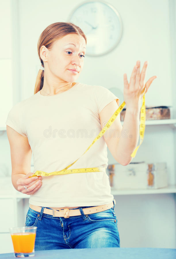 Frustrated woman measuring waist. Woman measuring waistline with yellow tape frustrated by increasing in volume stock images