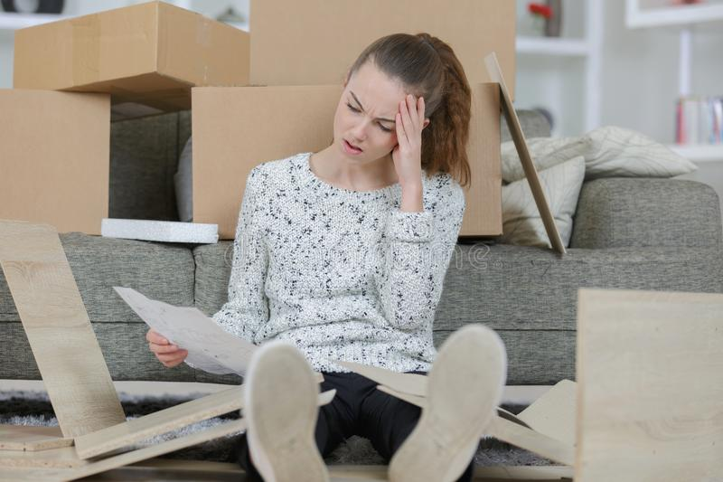 Frustrated woman putting together self assembly furniture royalty free stock photo