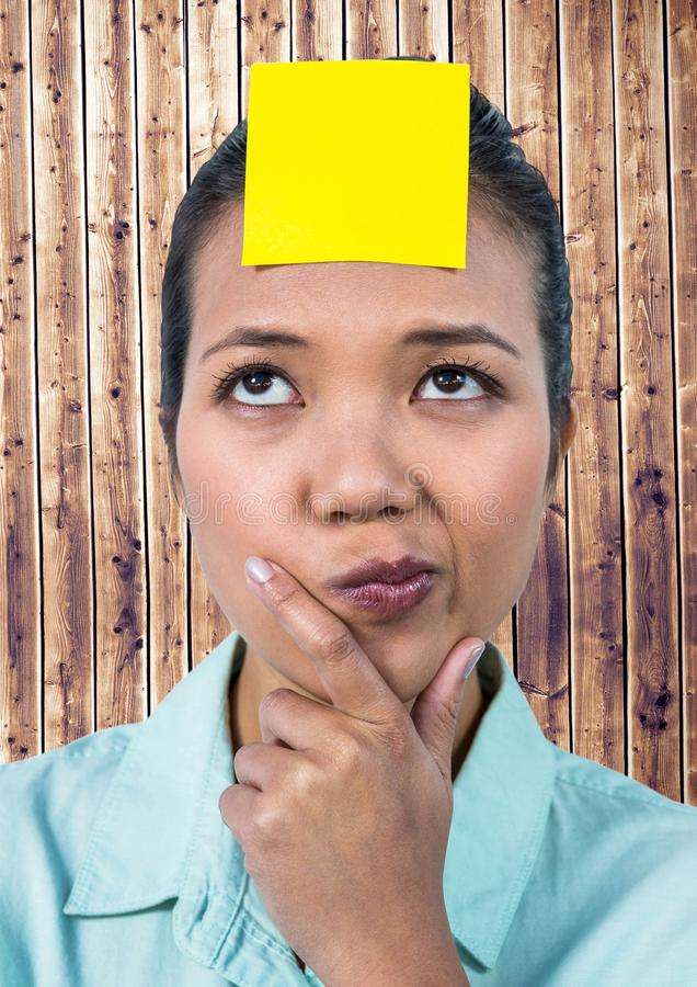 Frustrated woman with sticky note stuck on her forehead against wooden background stock image